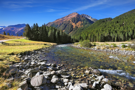 Idyllic landscape. Upper courses of falls - rather narrow fast seething small river among green mountain meadows.  National park Krimml falls in Austria