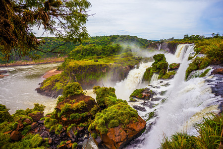 Powerful jets of the world famous waterfalls Iguazu. Travel to Argentina. Picturesque basaltic ledges form the waterfalls. The concept of exotic and active tourism Stock Photo