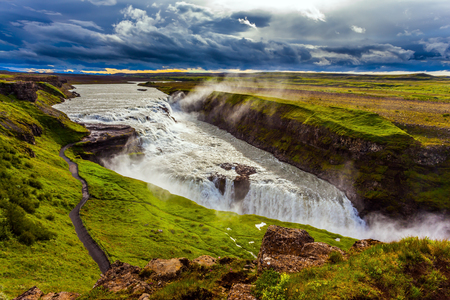 Fantastic Golden Waterfall Gulfoss in Iceland. On the shore is a path for tourists. Windy summer day. The concept of extreme and phototourism Stok Fotoğraf