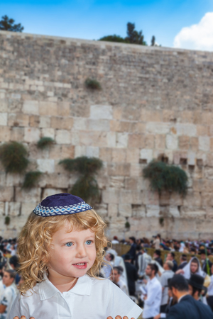 Lovely blonde boy with blue eyes in a skullcap. Autumn Jewish holiday Sukkot. The greatest shrine of Judaism is the Western Wall of the Temple