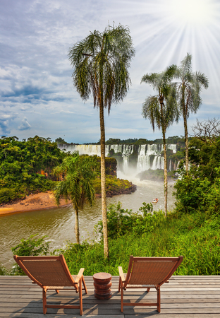 Two wooden chaise longue stand near the waterfalls. Scenic basaltic rock formations famous waterfalls Iguazu Falls. The concept of ecological tourism