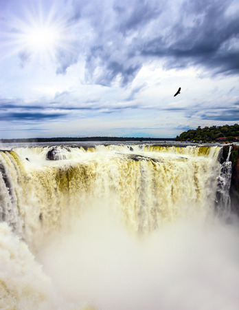 The autumn sun shines through the clouds. Andean condors fly above the roaring water. Devils Throat is the part of the Iguazu Falls. Concept of active and photographic tourism