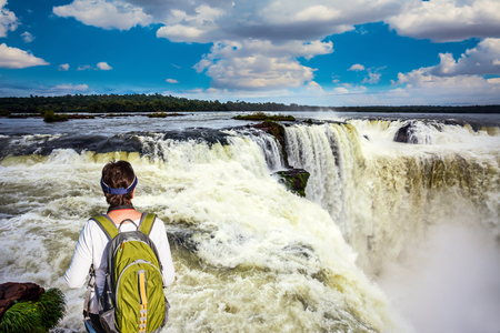 Energetic woman with a tourist backpack watching waterfalls the Garganta del Diablo Devils Throat. Concept of active and extreme tourism Stock Photo