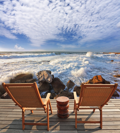 Charming lookout for two. Two convenient comfortable guest sun loungers and a bedside table are worth on a wooden platform. It is well-admired stormy sea surf Imagens - 95597666