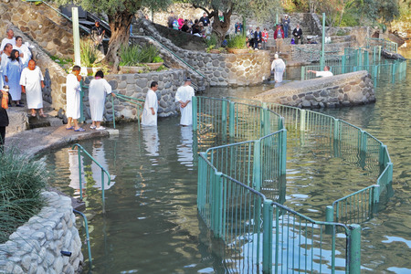 Yardenit, Israel - January 21: Baptism of Christian pilgrims in the holy waters of the Jordan River in the days of the Feast of Holy Baptism 21 January 2012 at Pilgrim baptismal site Yardenit, Israel. Pilgrims enter the water, dressed in special white chr Editorial