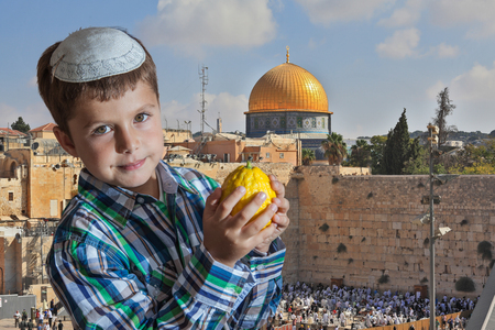 Cute seven year old boy in white skullcap with the etrog. Sukkot at the Western Wall of Temple in Jerusalem Stock Photo