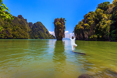 Woman performs yoga pose standing in the water of the Andaman Sea. Exotic vacation in Thailand