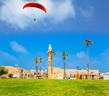 Israel. Sunny spring day. Ruins of the ancient city and port of Caesarea. In the blue sky flies a picturesque red parachute - wing. Concept of active, archeological and historical tourism
