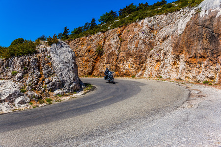 A lone motorcyclist on a steep turn of a mountain road  in the Provence. The fascinating journey to the canyon in Europe - Verdon. Concept of extreme and active tourism   Stock Photo