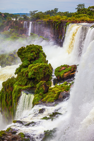 Powerful jets of the world famous waterfalls Iguazu. Picturesque basaltic ledges form the waterfalls. Travel to Argentina. The concept of exotic and active tourism