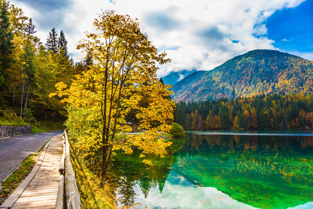 The road around the lake Lago de Fusine, is fenced with wooden handrails. Concept of cultural and ecological tourism. The smooth surface of the green water reflects the cloudy sky.