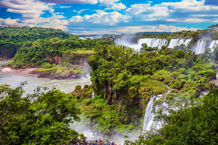 Travel to Argentina. Powerful jets of the world famous waterfalls Iguazu. Picturesque basaltic ledges form the waterfalls. The concept of exotic and active tourism