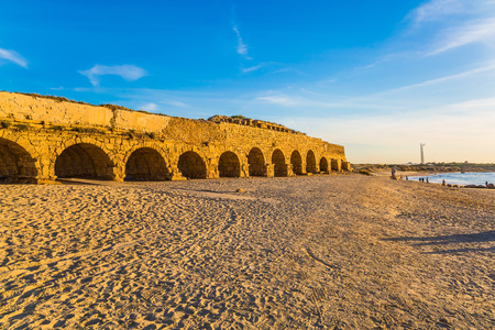 Fantastic sunset on the Mediterranean coast in Caesarea. High aqueduct, built under the reign of Herod the Great. Concept of active, ecological and historical tourism