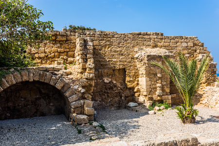 The oldest amphitheater in Israel, a fragment of protective walls. Sunny spring day. Ruins of the ancient city of Caesarea. Concept of archeological and historical tourism