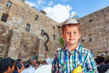 People in white Taliths pray at the Western Wall of the Temple. Beautiful Jewish boy in white skullcap, with etrog. Autumn Jewish holiday Sukkot