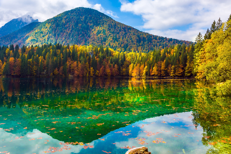 The quiet lake in Northern Italy, Lago de Fusine. The smooth surface of the water reflects the cloudy sky and multicolored forests. Concept of cultural and ecological tourism Imagens