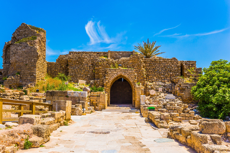 Ruins of the ancient city of Caesarea. The oldest amphitheater in Israel, a fragment of protective walls. Sunny spring day. Concept of archeological and historical tourism
