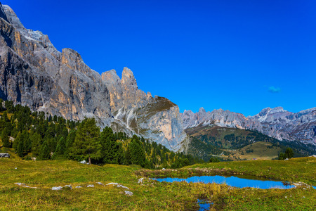 Southern Limestone Alps. The majestic white and gray rocks of the Italian Dolomites. Small puddle picturesquely reflects the blue sky. The concept of active and car tourism