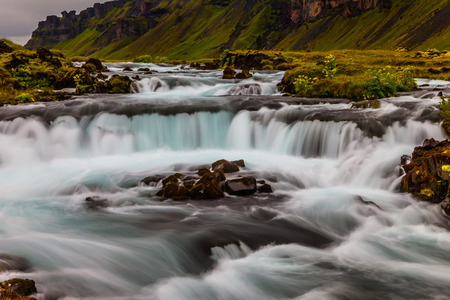 Main road number 1 around the island. Powerful cascading waterfalls in Iceland. Travel in July. Concept of active and extreme tourism 写真素材