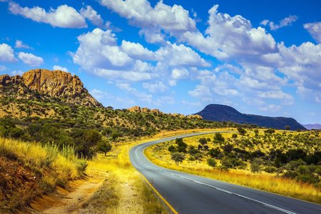 Asphalt road in Namibia. Gorgeous autumn turned yellow bush and mountains in the distance