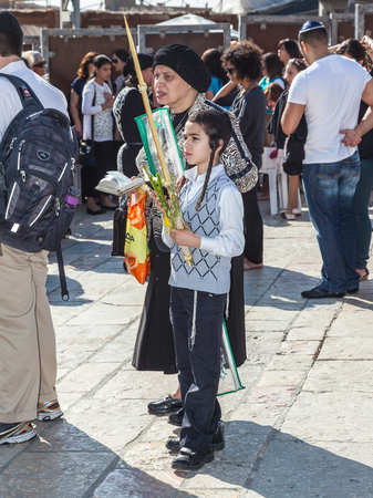 JERUSALEM, ISRAEL - OCTOBER 12, 2014: The area in front of Western Wall of Temple filled with people. Morning autumn Sukkot. Many believers have brought prayer books and four ritual plants Editorial