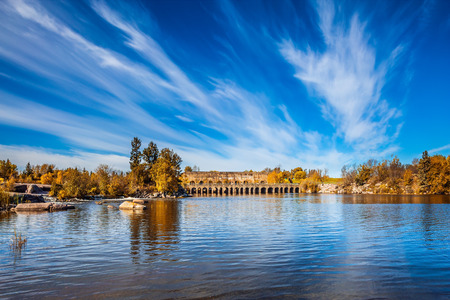 Cirrus clouds are reflected in the Winnipeg River. Wonderful day in Manitoba, Canada. Old Pinawa Dam Park. The concept of ecological and recreational tourism