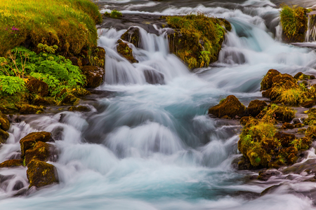 Boiling and rumbling cascading waterfall in Iceland. Wide picturesque valley along highway number one around the island. Travel in Iceland. Concept of active and extreme tourism