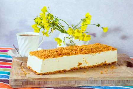 The vase with daisies and porcelain cup with hot tea. Professional bakery. White cheesecake, sprinkled with sweet crumbs Stock Photo
