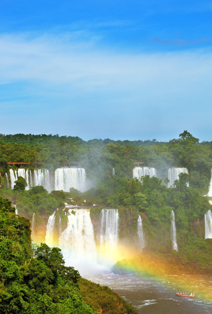 The most famous waterfalls in the world - Iguazu. Magnificent rainbow is above the thundering water jets.