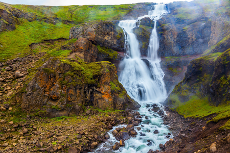 Concept of active and extreme tourism. Powerful streams of cascade falls with a roar break against cold rocks. Cold and rainy July in Iceland Stock Photo