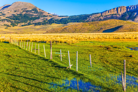 The Argentine Patagonia. The huge possessions of hacienda are surrounded by distant mountains. The green grass field is impregnated with streams. The concept of exotic and active tourism Stock Photo