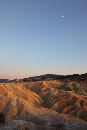 Moon over sand waves of the famous Zabriskie - Point.  Pink sunset in Death Valley.