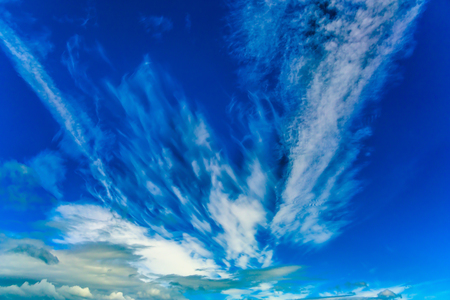 Cirrus clouds of fanciful shapes in the blue sky of Australia. Travel to the edge of the earth. The concept of photo and ecological tourism