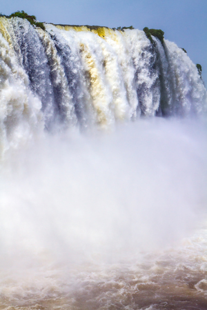 Rumbling world of falling water. Iguazu Falls in South America, on the border of three countries: Brazil, Argentina and Paraguay. Concept of active and extreme tourism