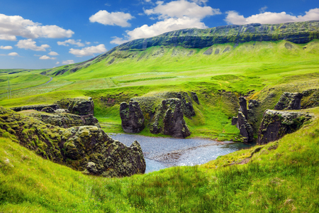 The striking canyon in Iceland. Green Tundra in July. The concept of active northern tourism. Bizarre shape of cliffs surround the stream with glacial water 版權商用圖片