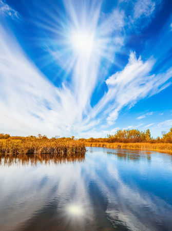 The concept of ecological tourism. Weak northern autumn sun and thin cirrus clouds is reflected in the Winnipeg River. Old Pinawa Dam Provincial Heritage Park Stock Photo