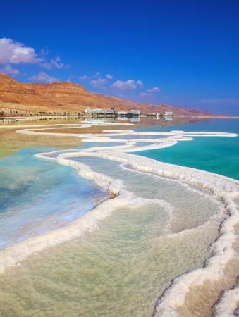 Der Weg vom Salz kräuselt sich malerisch in salzigem Wasser. Hotels spiegeln sich in glattem Wasser an Land wider. Israelische Küste des Toten Meeres