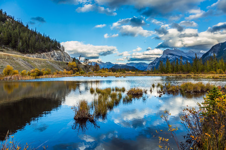 Autumn day on the lake Vermilion. Lush cumulus clouds are reflected in the smooth water of the lake. The concept of ecological, photographic and active tourism