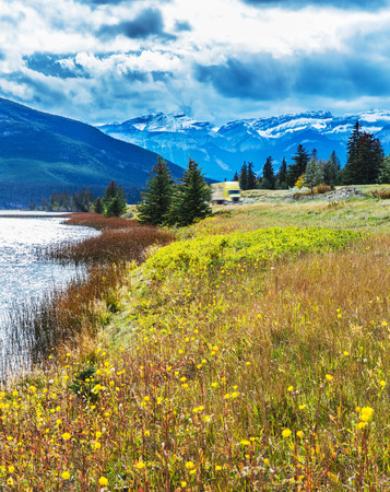 Rocks, lakes and yellow grass under flying clouds. Impressive trip to the Rockies of Canada. Concept of active automobile and ecological tourism