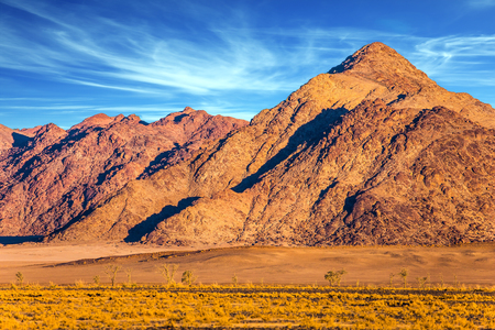 Purple and yellow mountains of the Namib desert. Sunset, Namibia. The concept of extreme and exotic tourism