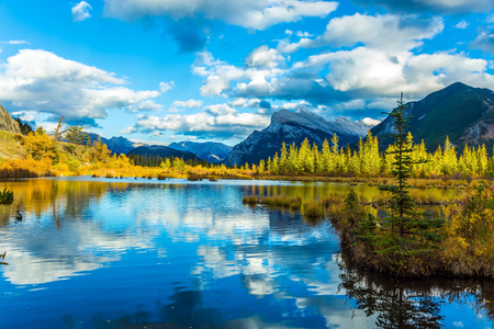 Lush clouds are reflected in the water of the lake. Warm autumn day on the lake Vermilion. The concept of ecological, photographic and active tourism