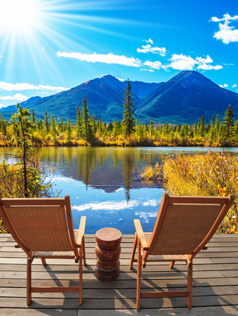Indian summer in the Rocky Mountains of Canada. Two comfortable wooden chairs and a small round table on the lake. Concept of ecological tourism