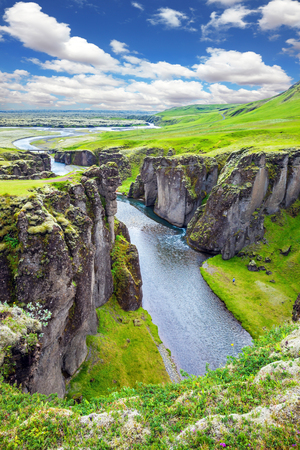 Bizarre shape of cliffs surround the stream with glacial water. The striking canyon in Iceland. The concept of active tourism Reklamní fotografie