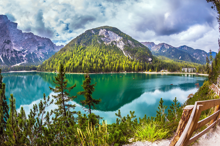 The pedestrian footpath around the lake is fenced with a wooden handrail. Magnificent Alpine lake Lago di Braies. Concept of ecological and pedestrian tourism Banque d'images