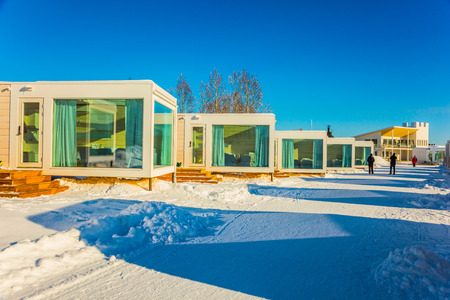 ROVANIEMI, LAPLAND, FINLAND - MARCH 7, 2017. Magnificent hotel in Lapland. Concept of active and exotic tourism Crouching road in the snow-covered aspen grove. Bright winter frosty day