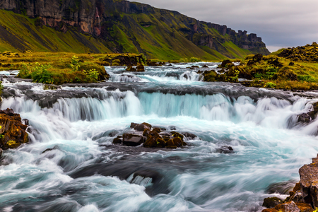 Powerful cascading waterfalls in Iceland. Main road around the island. Travel in July. Concept of active and extreme tourism