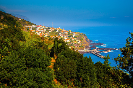 The picturesque village with red roofs on the cape is surrounded by forest. The magical tropical island of Madeira. Concept of exotic and ecological tourism