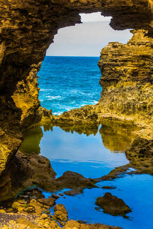 The concept of exotic, active and photo-tourism. Great Ocean Road of Australia. Coastal rocks formed a picturesque arch of sandstone. Puddle of quiet water in an arch