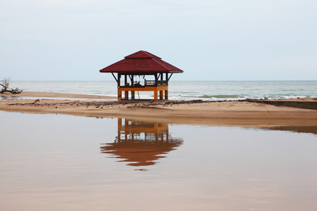 Sandy beach on Koh Samui. The beach wooden arbor is picturesquely reflected in water Фото со стока