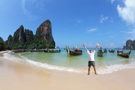 Happy man joyfully welcomes the sunrise. A picturesque ocean bay in the Thai gulf Banco de Imagens